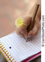 Children hand with funny yellow ring writing on a notebook -...