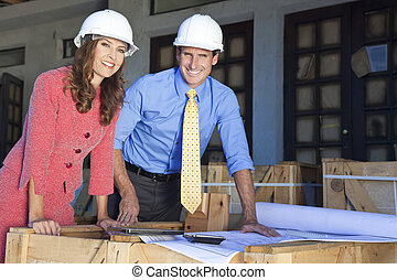 Man & Woman In Hard Hats on Construction Site - Man in hard...