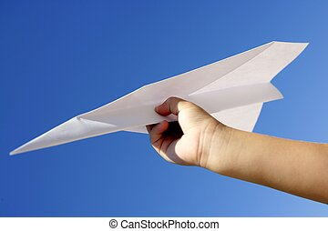 Paper airplane in children hand over blue sky - Paper...