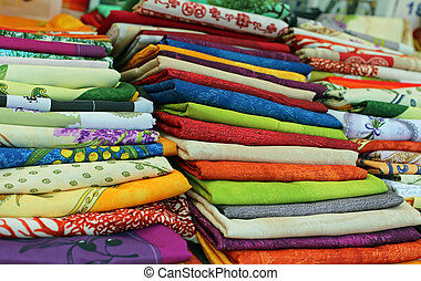 lots of colored cloth tablecloths for sale in the city...