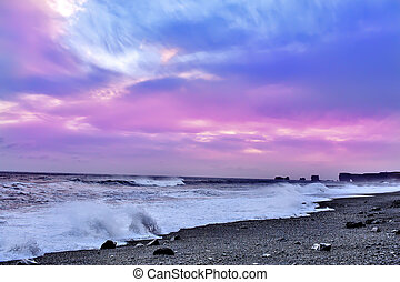 Pink sunset - Surf on the black beach with black sand at...