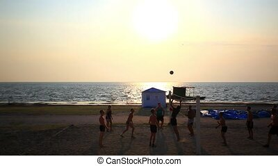 Russia. Primorskiy kray. 16 august 2014. Group of young people playing volleyball on the beach during sunset. HD. 1920x1080