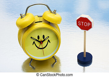 Stopping Time - A yellow retro smiley face clock sitting...