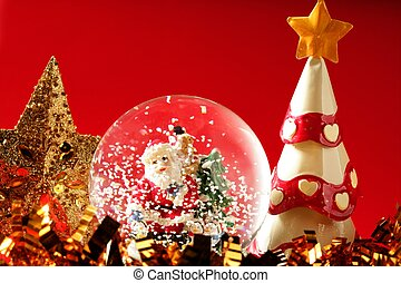 Santa claus figurine on a glass snowing ball, red background...
