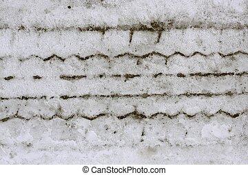 Snow macro detail of car weel footprint