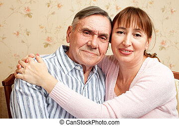 Senior man, woman with their caregiver at home - Happy...