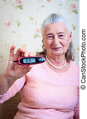 Woman testing for high blood sugar Woman holding device for...
