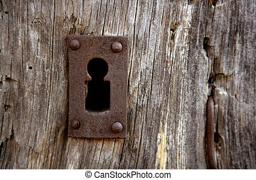 Key hole over aged gray old wood, rusty metal