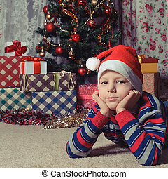 dreaming boy in front of the christmas tree