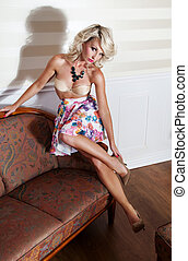 Sensual blonde woman posing in fashionable skirt and...
