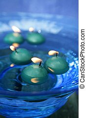 green candles over blue glass bowl of water