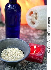 Aromatherapy, red candle, marine natural sponge and bowl of...