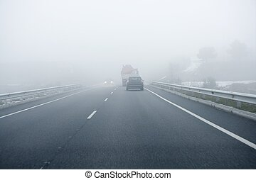 Foggy gray road, cars driving into the fog