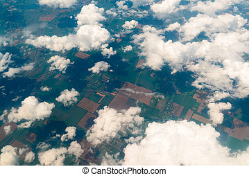 View of land, fields, and clouds from above - View of the...