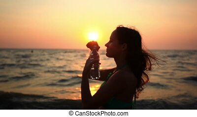 Woman drinking from a Water Bottle at Sunset on the beach....