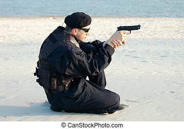 security man - The security man with gun is on sand.