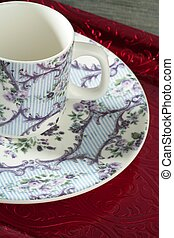England old style tea cup and dish over red tray and blue...