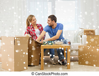 smiling couple opening cardboard box with dishes - repair,...
