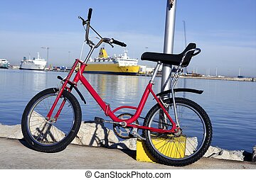 bicycle parked in a harbour over blue water