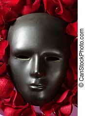Black carnival mask with red rose petals around