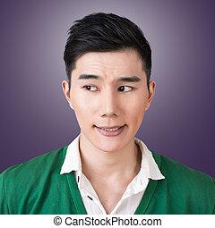 Funny facial expression, closeup Asian young man