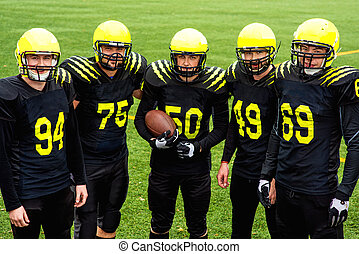 American football team in sportswear with the ball standing...