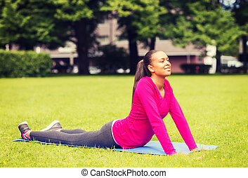 smiling woman stretching on mat outdoors - fitness, sport,...