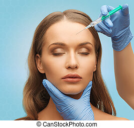 beautiful woman face and hands with syringe