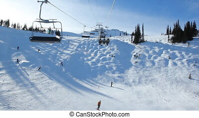 Skilift and moguls. - Riding on a chairlift with view of...