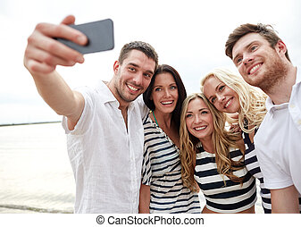 happy friends on beach and taking selfie - summer, sea,...