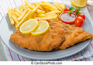 Schnitzel with french fries and a spicy dip, fresh from red...