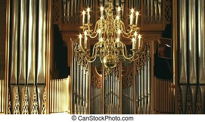 church organ front behind chandelier - tilt up - church...