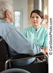 Disabled man talking with nurse - Disabled man using...
