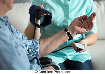 Nurse measuring blood pressure of handicapped man