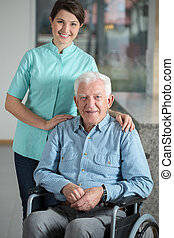 Elegant man using wheelchair and his kindly nurse
