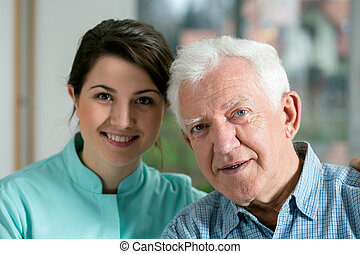 Smiling senior man and young nurse - Portrait of smiling...