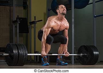 Bodybuilder Doing Deadlift For Back - Male Fitness Athlete...
