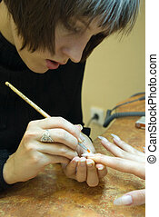 manicure master making nail painting in beauty salon -...