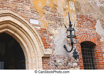 Medieval luminaire on old brick wall of a house
