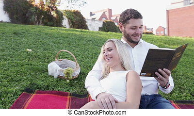 Couple on lawn reading book and smile