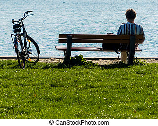 man takes a break with bike - a man sitting pensively in a...