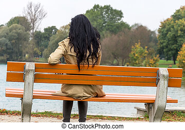 young woman thoughtfully - a young woman sitting on a park...