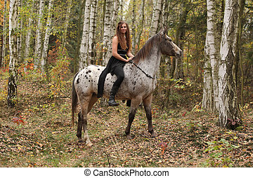 Young girl with appaloosa horse in autumn forest