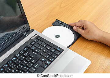 Hand inserting a cd on laptop on table