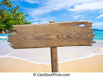 old wooden signboard on tropical beach - old wooden plate on...