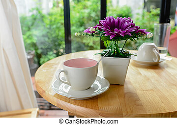 Coffee mug and flower pot on wooden table
