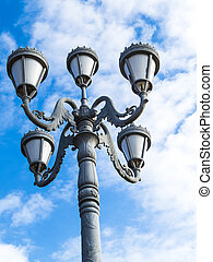 Streetlight against the blue sky with white clouds