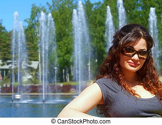 Woman in a park - A woman with brown curly hair is wearing...