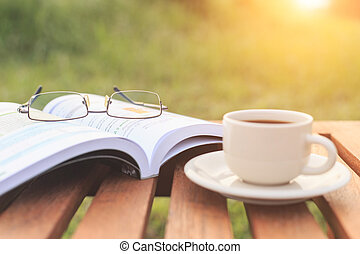 Close up glasses on book and Coffee cup on the table in the...
