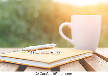 Sunday written in letter beads and a coffee cup on table